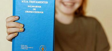 Mynd af barni með Nýja testamentið